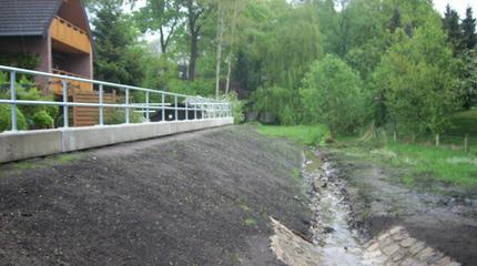 Hochwasserschutzmaßnahme Augustdorf, Anschichten des wasserseitigen Dammes mit Teilpflasterung des Bachbettes